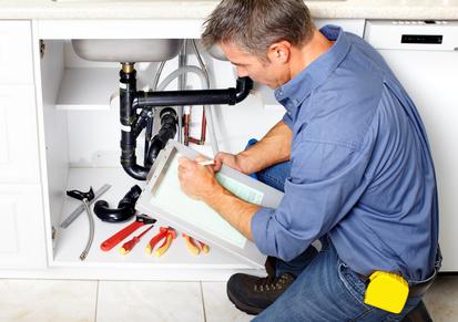 plombier qui calcule le prix des réparations à un évier