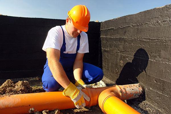 plombier qui installe un tuyau pvc