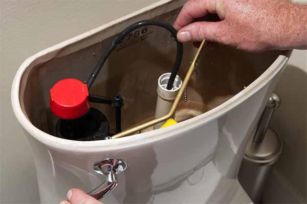 plombier qui répare le wc