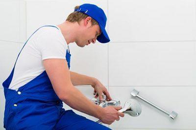 plombier qui répare une douche qui fuit