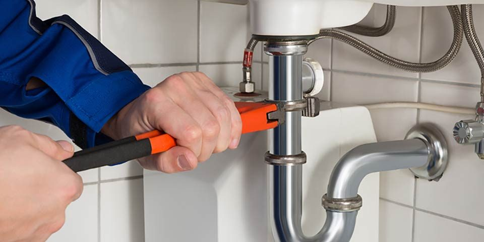 plombier qui répare la tuyauterie évier